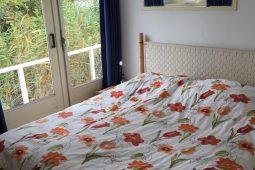 slaapkamer met tweepersoons bed en openslaande deuren