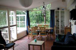 woonkamer met eethoek en openslaande deuren naar het terras